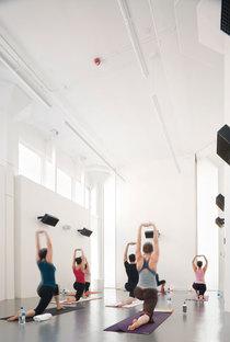 Una delle sale dello yoga: il bianco criduce l''impatto degli impianti a vista