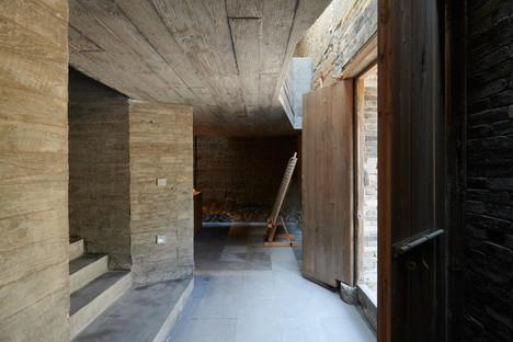 Casa ristrutturata e trasformata in libreria con cemento e acciaio di TAO Architects
