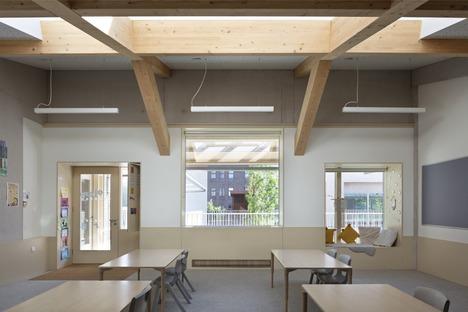 Torre di appartamenti con scuola in mattoni, cemento e legno